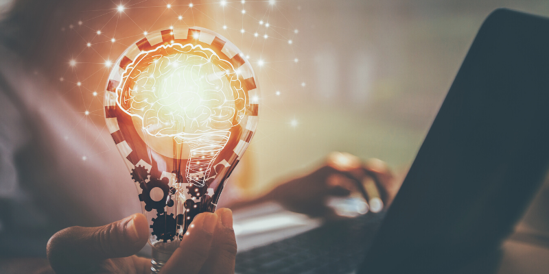 mano che tiene lampadina con rotelle che rappresentano la tecnologia nella proprietà intellettuale
