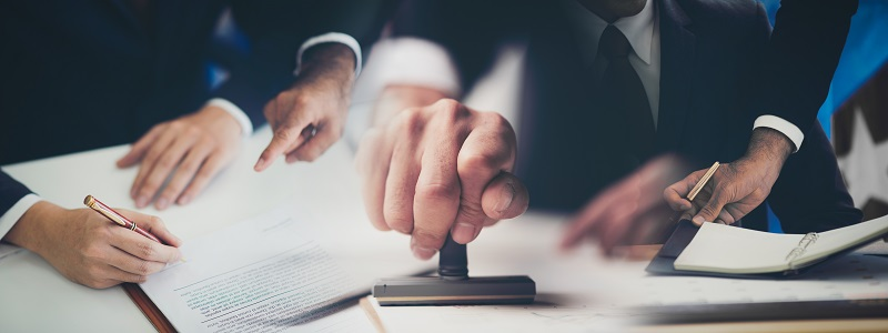 primo piano della mano di una persona che firma un documento e lo timbra